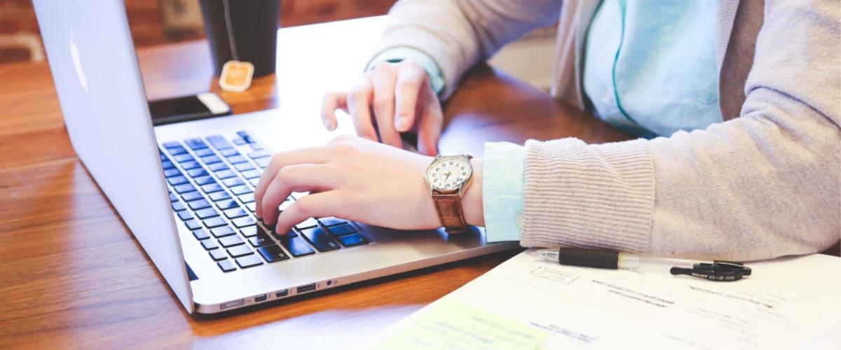 mains travaillant sur ordinateur, avec cahier, relations presse, média
