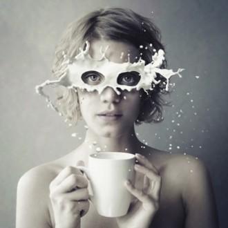 femme tenant une tasse éclaboussée de lait comme un masque, la vision de la communication selon l