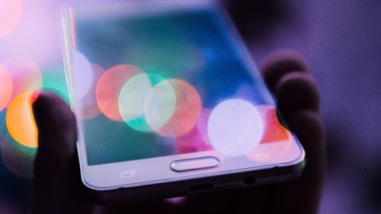 main tenant un portable, reflets de lumière, social média, engagement réseaux sociaux